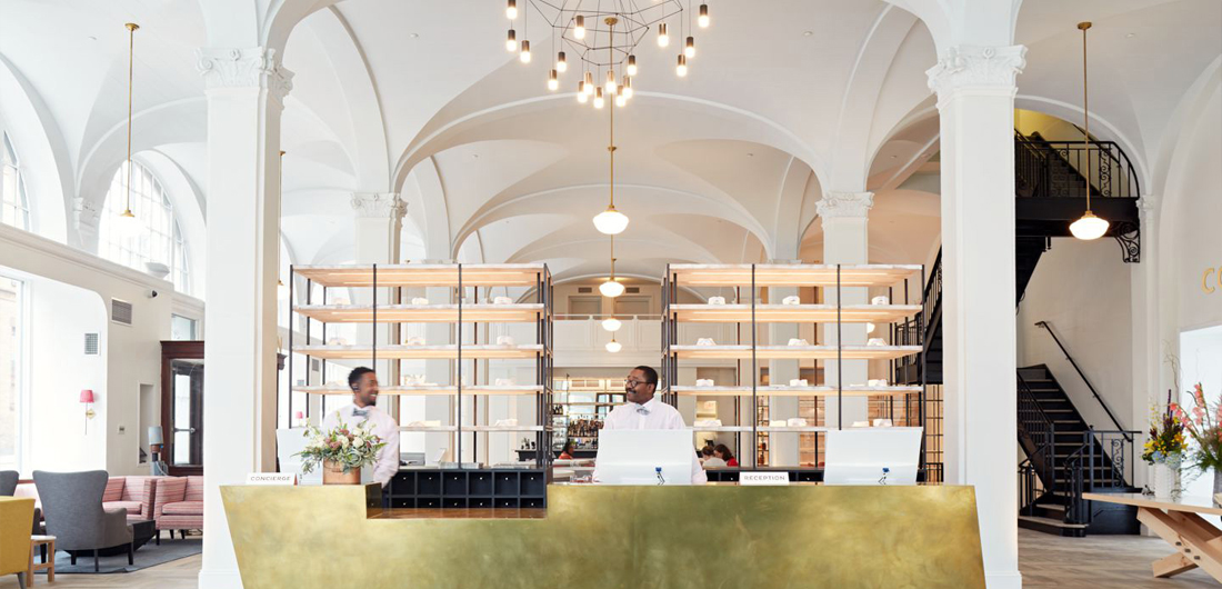 two men at hotel lobby front desk in Richmond, Virginia, hospitality branding in VA by creative agency